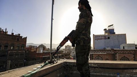 Et medlem af en sikkerhedsstyrke,  som er loyal over Yemens iransk-støttede Houthi-oprørere, holder vagt under en protestaktion vendt mod USA i hovedstaden Sana.