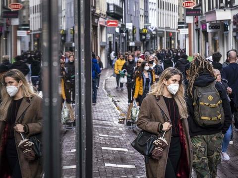 Mange af de handlende på et strøg i Amsterdam bærer mundbind. Nu skærper Hollands regering restriktionerne i et forsøg på at få bugt med coronasmitten.
