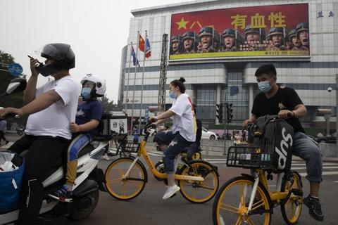 Kineiske indbyggere kører forbi militærets propaganda  sidste år. Nu deltager mange almindelige kinesere i en ordkrig mod USA og EU. pro