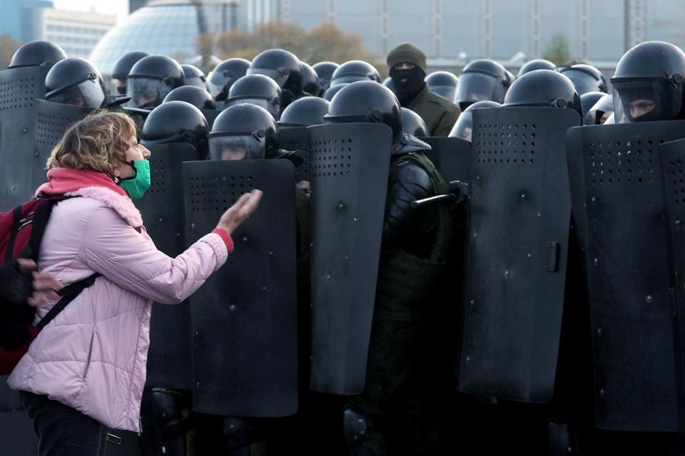 En kvinde diskuterer med betjente i kampudstyr, der søndag holder centrum af Minsk belejret under nye store protester mod regimet.