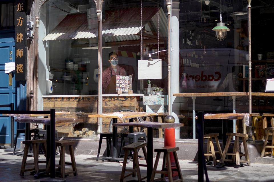 En ansat kigger ud fra vinduet fra en restaurant i Chinatown i London. Udendørs spisning er tilladt nu - og fra på mandag må gæsterne også rykke indendørs.