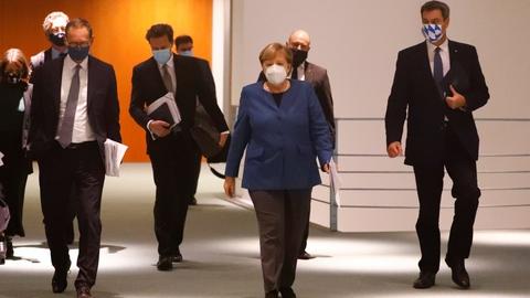 Forbundskansler Angela Merkel ankommer til onsdagens pressemøde om nedlukninger i Tyskland sammen med Bayerns ministerpræsident,  Markus Söder og Berlins borgmester, Michael Müller.