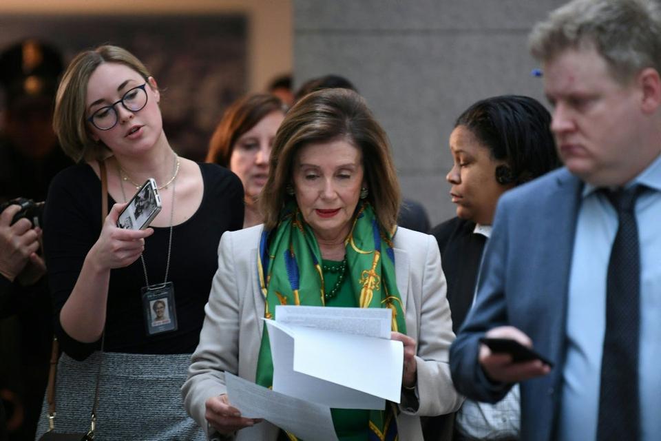 Omgivet af journalister ankommer formanden for Repræsentanternes Hus, demokraten Nancy Pelosi, til et lukket møde med sine partifæller i Kongressen tirsdag morgen lokal tid.