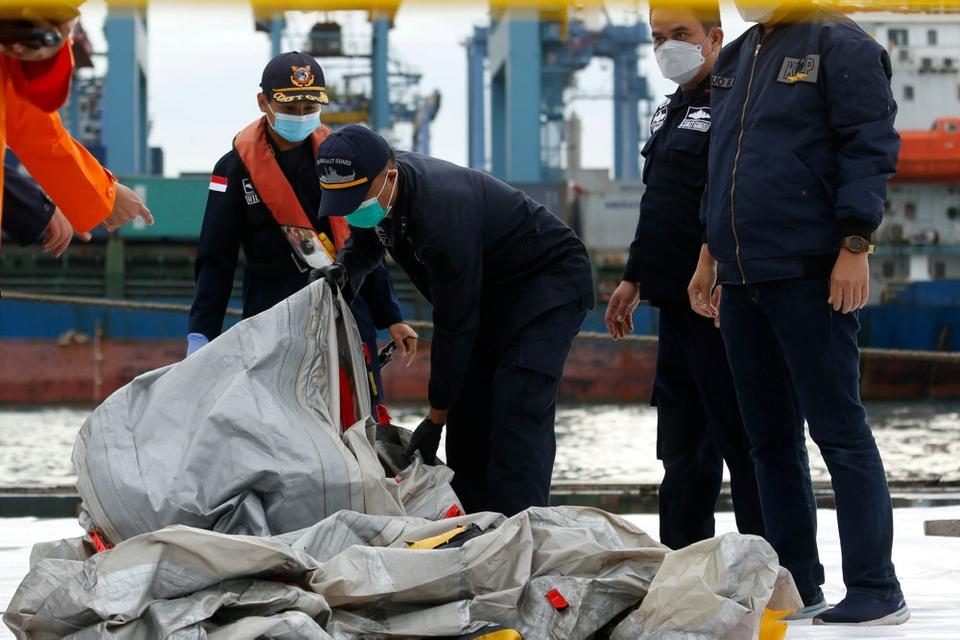 Indonesiske redningsfolk bærer det, der menes at være resterne af et Sriwijaya Air-fly, der styrtede ned i havet ud for Jakarta lørdag.