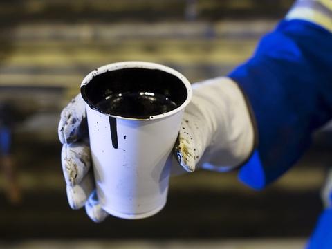 En arbejder holder en stor kop med olie. Ifølge en rapport bør Norge stoppe med at lede efter fossilt brændsel, lade være med at udvide infrastrukturen i industrien og forbyde de mest forurenende og miljøskadelige former for olie- og gasudvinding.