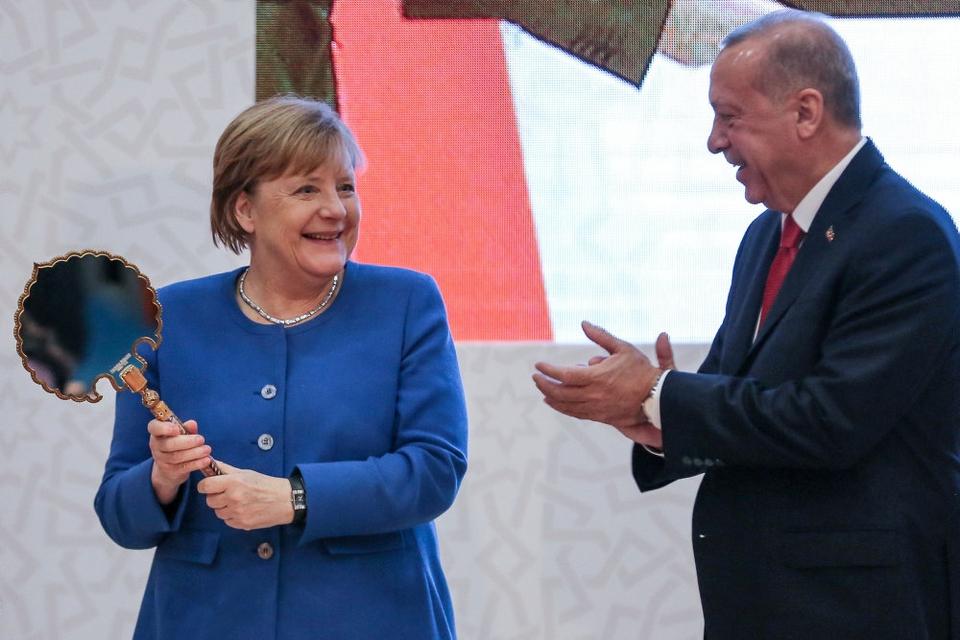 Tysklands forbundskansler, Angela Merkel, viser en gave frem, som hun har fået af den tyrkiske præsident, Recep Tayyip Erdogan, under sit besøg i Istanbul fredag.