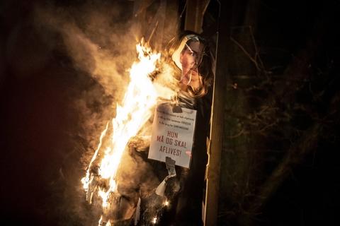 Dukke med foto af statsminister Mette Frederiksen brændes i forbindelse med at gruppen Men in Black afholder demonstration i København, lørdag den 23. januar 2021.