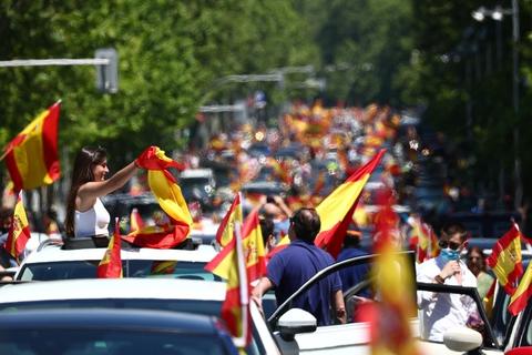 Demonstranter med spanske flag kørte lørdag gennem Madrids gader i en drive-in demonstration indkaldt af højrefløjspartiet Vox. Også i flere andre byer var der demonstrationer mod regeringens håndtering af coronakrisen og ikke mindst nedlukningen og de konsekvenser, den har for den spanske økonomi.