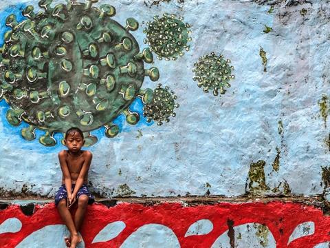 En dreng sidder under et murmaleri af coronavirusset i Vestjava i Indonesien. Landet har bekræftet over 278.000 tilfælde af coronasmitte og har ifølge de officielle tal lidt over 10.400 dødsfald blandt smittede.