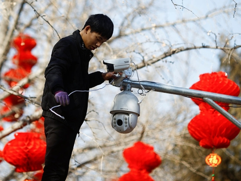 Overvågningsudstyr fra det kinesiske selskab Hikvision - som her sættes op af en medarbejder i Ditan Park i Beijing - er blevet købt af flere danske offentlige institutioner, selv om de ifølge den amerikanske regering bruges til undertrykkelse i Kina. (Arkivfoto)