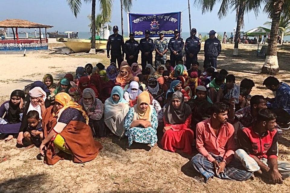 En del af de overlevende fra forlis i Den Bengalske Bugt ses her på en strand i Bangladesh, efter at de var blevet reddet i land af kystvagten.