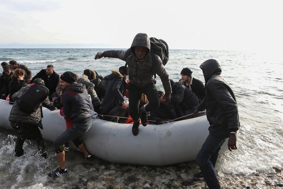 Migranter fra Syrien, Irak og Afrika springer af en gummibåd på den græske ø Lesbos sømdag morgen efter at være afsejlet fra Tyrkiet.