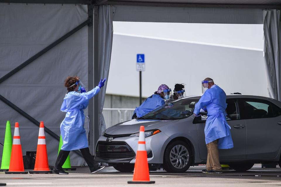 Florida er en af de mindst 18 delstater, som har oplevet mere end en fordobling i antallet af smittetilfælde i juli. Her ses medicinsk personale i Florida teste en borger for coronavirus.