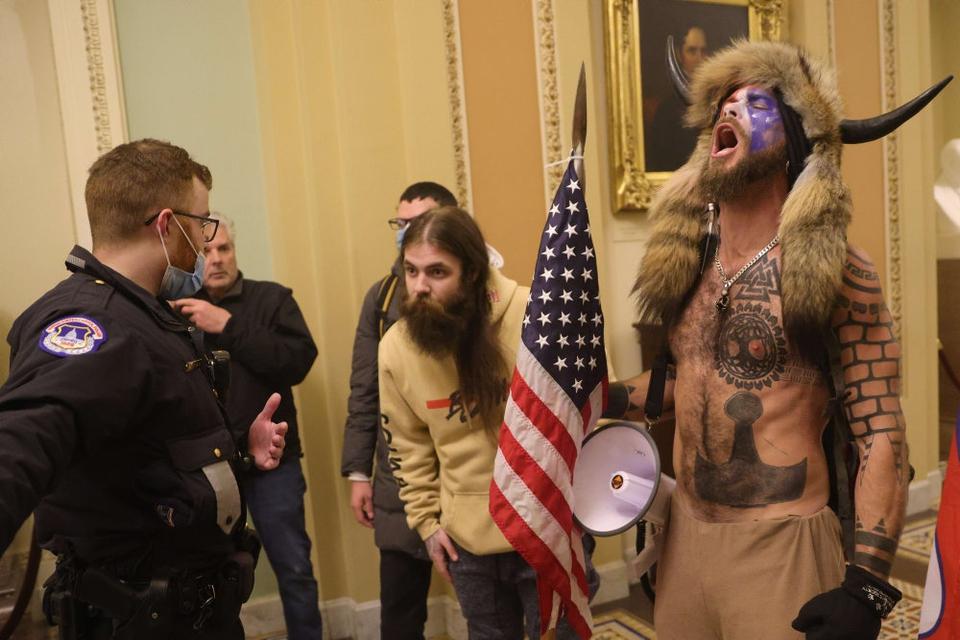 """En ledende figur i den kontroversielle konspirationsbevægelse QAnon ved navn Jake Angeli også kendt som """"Q Shaman"""" spillede en synlig rolle under onsdagens optøjer i Kongressen."""