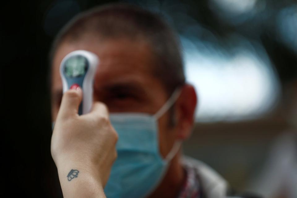 Socialarbejder Tamara Corona tager en besøgendes temperatur på et plejehjem ved Madrid.