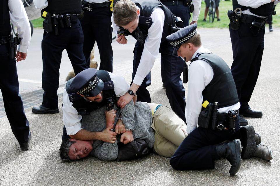 Demonstant overmandet af politi i Hyde Park efter coronakrisens udbrud. Den britiske anklagemyndighed forbereder over 300 straffesager mod personer, som har spyttet eller hostet på politifolk og hospitalsansatte og derefter sagt, at de var syge med Covid-19.