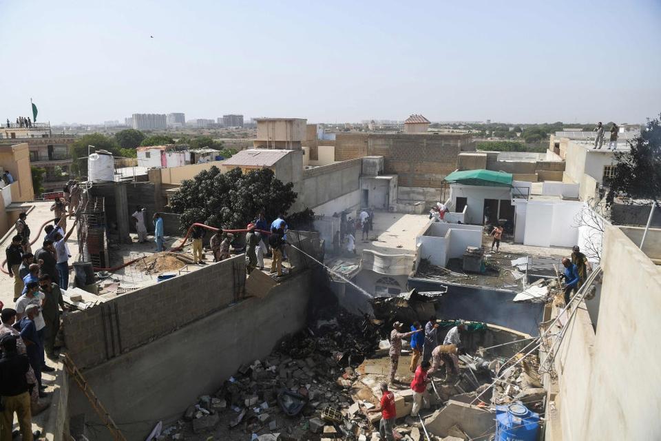 Redningsarbejdere sprøjter her vand på dele af det forulykkede fly i millionbyen Karachi.