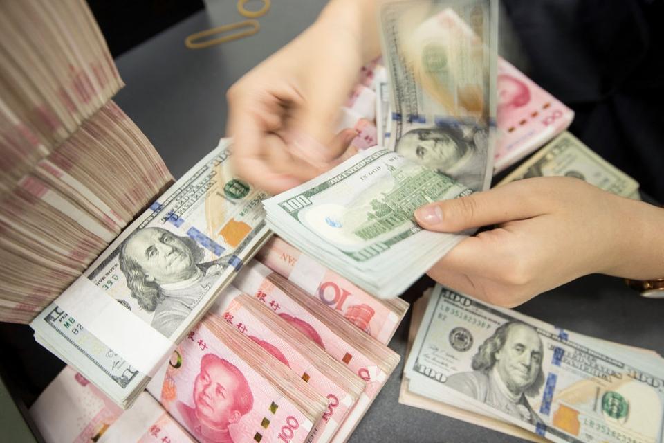 USA beskylder ikke længere Kina for at fuske med sin valuta. Mandag har det amerikanske finansministerium således fjernet betegnelsen valutamanipulator, som USA officielt hæftede på Kina i august 2019. Her ses en ansat i en kinesisk bank tælle yuan og dollarsedler. (Arkivfoto).