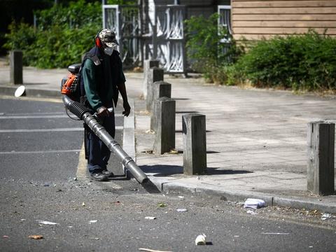 En arbejder rydder op efter hårde sammenstød i Brixton syd for London natten til tordag, hvor deltagere i et ulovligt musikarrangement ignorerede tilkaldt politi. Derefter kom det til hårde sammenstød.