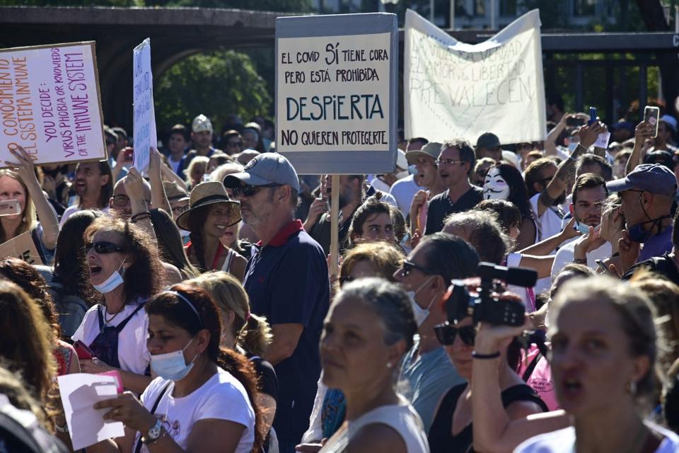 En folkemængde med klappende og jublende mennesker samledes søndag under et enormt gult og rødt spansk falg på Plaza Colon i den centrale del af den spanske hovedstad. De protesterede mod obligatorisk brug af mundbind og andre restriktioner vendt mod covid -19.