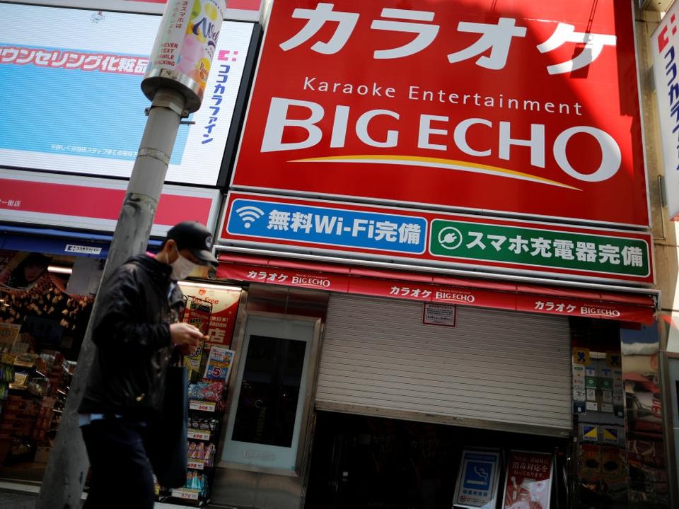 Mand med beskyttelsesmaske foran midlertidigt lukkede karakokeklubber i Tokyo. Men karaokeentusiaster i Japan kan nu igen komme til at synge, hvis de er forsigtige under deres optrædener.
