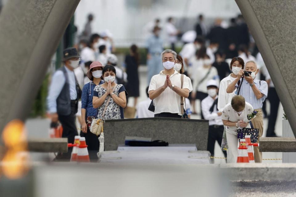 Folk beder for ofrene for atombomben i 1945 med masker på under en ceremoni i Fredsmindeparken i Hiroshima.