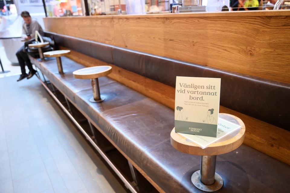 Et skilt opfordrer kunder i butikscenteret Gallerian i Stockholm til at sidde ved hvert andet bord under coronakrisen.