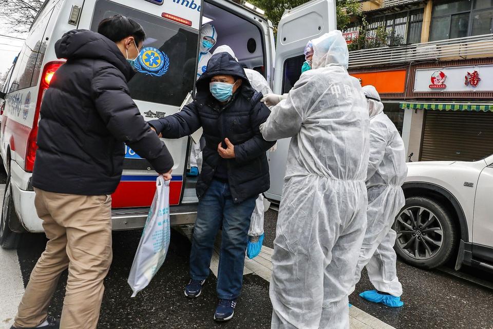 En patient bliver hjulpet ud af en ambulance af lægefolk med beskyttelsesmasker og dragter, der skal hindre smittte af den dødelige virus. Wuhan i Kinas Hubei-provins er epicenteret for coronovirusset. (Foto: AFP/Ritzau Scanpix)