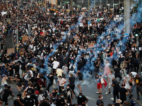 Demonstranter flygter fra politiets tåregas under en demonstration i Paris tirsdag.