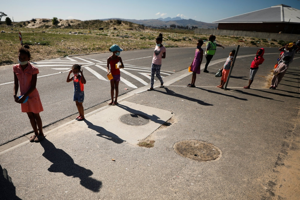 Nedlukning af skoler og påbud om at undgå fysisk kontakt udløser angstfølelser hos mange børn. Det fremgår af en ny rapport fra Red Barnet. Arkivfoto er fra Sydafrika, hvor børn står i kø til et måltid mad.
