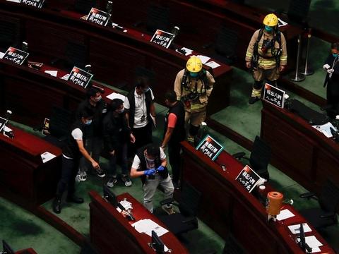 Brandfolk tjekker ildelugtende gødning, som en kritisk lovgiver hælder ud i Hongkongs parlament under en ophedet debat om Kinas nationalsang. Det ses af oppositionen som et nyt forsøg fra Kina på at fravriste bystatens dets selvstyre.