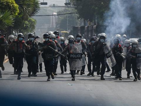 Kampklædte betjente er lørdag på gaden i Myanmars største by, Yangon.
