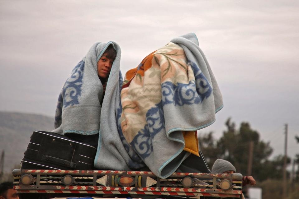 Syriske børn har pakket sig ind i tæpper, mens de den 11. februar 2020 sidder bag på en lastbil nær byen al-Ghazawiya og flygter fra angreb på landbrugsområder vest for Aleppo.