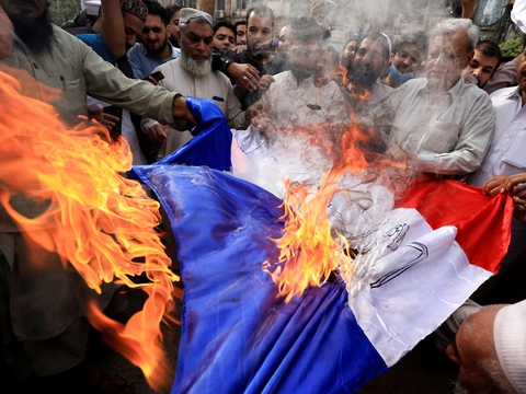 People chant slogans as they set fire to a Frances flag during a protest against the cartoon publications of Prophet Mohammad in France and comments by the French President Emmanuel Macron, in Peshawar, Pakistan October 28, 2020. (Foto: Fayaz Aziz/Reuters/Ritzau Scanpix)