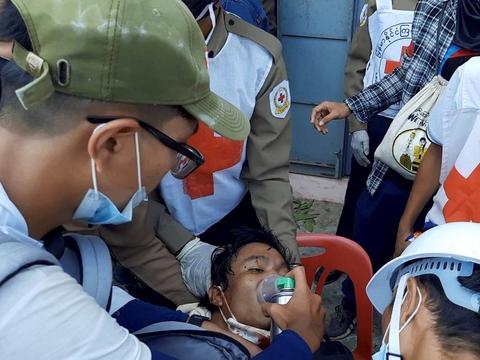 Læger forsøger at redde en demonstrant, som er blevet ramt af skud i Dawei i Myanmar søndag.