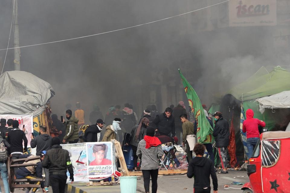 Irakiske demonstranter går rundt blandt brændende telte på Tahrir-pladsen i Bagdad, som sikkerhedsstyrker forsøgte at rydde lørdag.