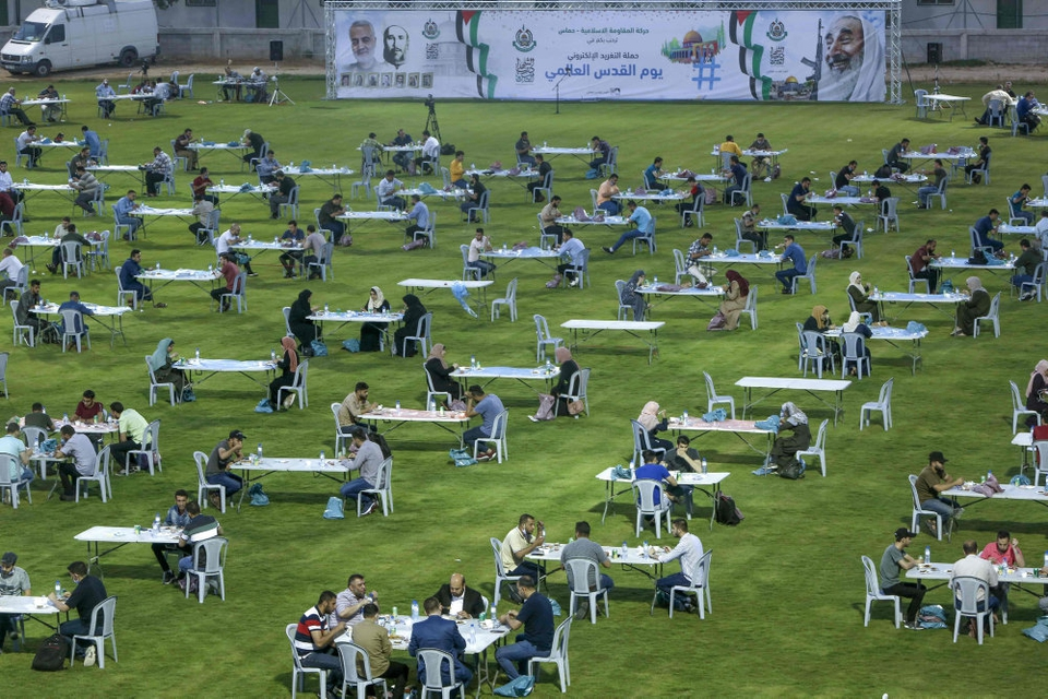 Med behørig afstand mellem sig indtog palæstinensere i Gaza fredag aften iftar-måltidet, der afslutter den daglige faste under ramadanen. Hamas-bevægelsen, der kontrollerer Gaza, havde opstillet hundredvis af borde på et fodboldstadion i Gaza City.