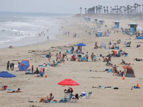 Folk er taget på stranden på Huntington Beach i Californien i USA, som fortsat er blandt de værst ramte lande i verden. (Arkivfoto.)