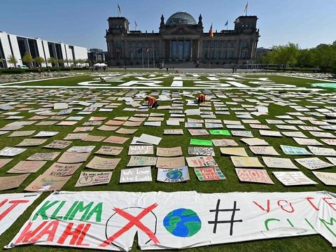 """Skilte på græsset foran Reichstag-bygningen under en """"Fridays for Future""""-klimademonstration den 24. april 2020 i Berlin. (Foto: John Macdougall/AFP/Ritzau Scanpix)"""