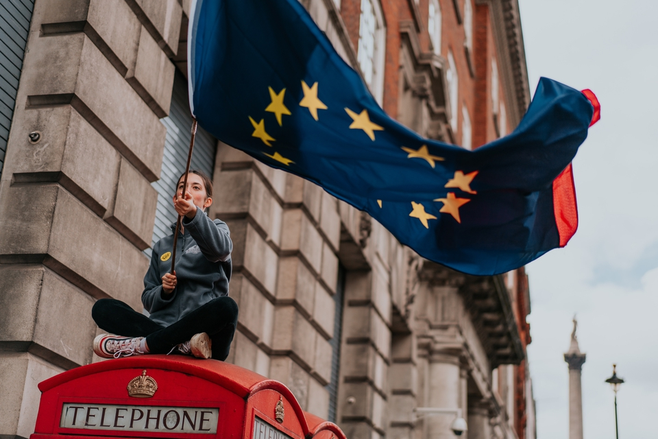 En EU-tilhænger vifter med unionens flag på toppen af en britisk telefonboks. (Foto: Brunel Johnson/Unsplash)